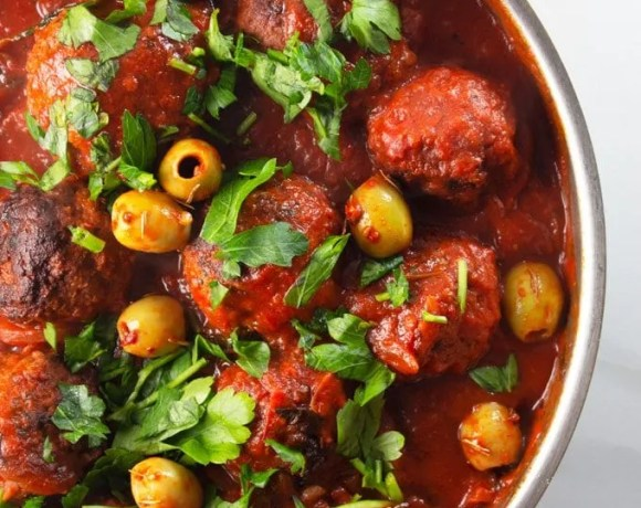 Moroccan Meatballs with marinara sauce in a skillet topped with coriander and olives