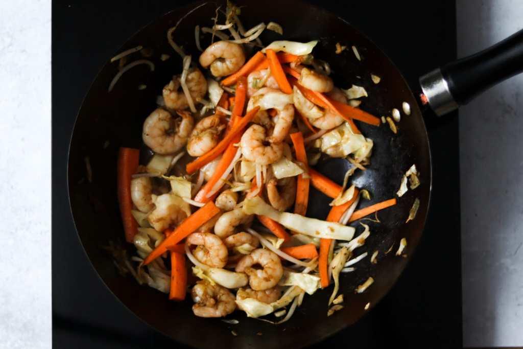 Vegetables and king prawns being stir-fried in wok.