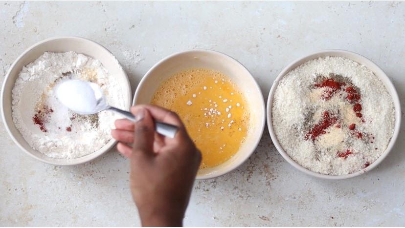 Adding seasonings to plain flour and breadcrumbs