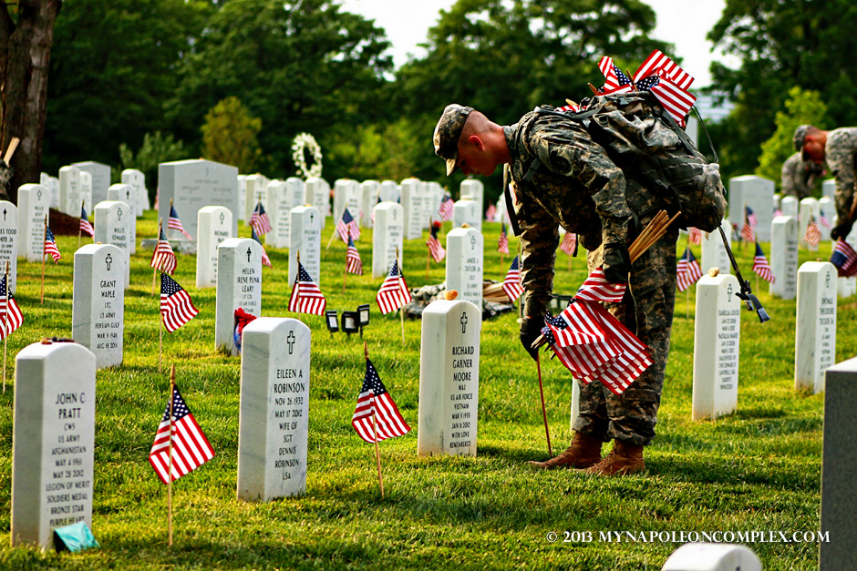 Soldier inserting American flag at a tomb in Arlington.