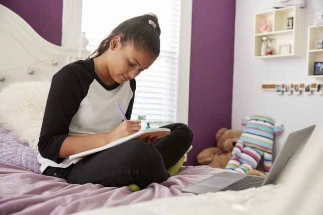 Young teen girl sitting on her bed writing in a notebook