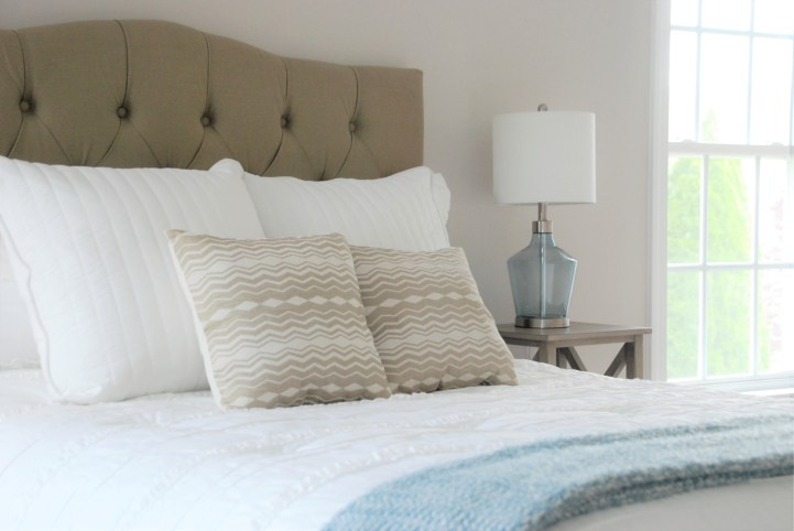 Picture of a tan headboard and tan and blue accents in a master bedroom