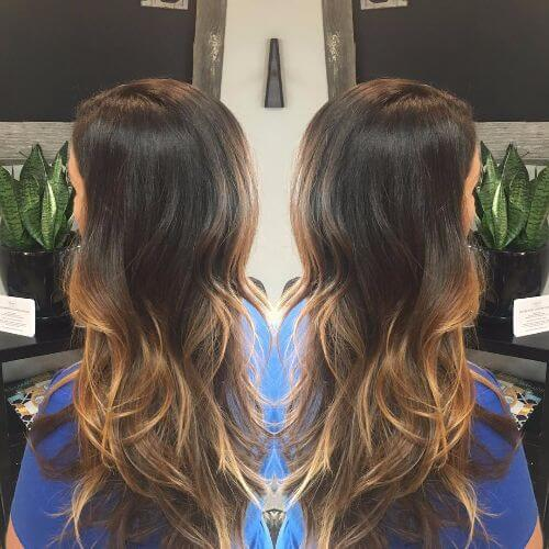 caramel highlights on loose waves of ash brown hair
