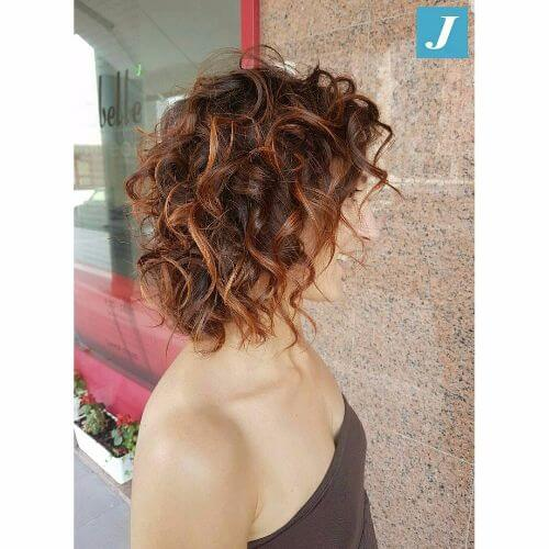curly lob hairstyle with caramel balayage