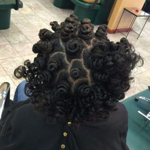Woman with bantu knots sitting on hair salon chair