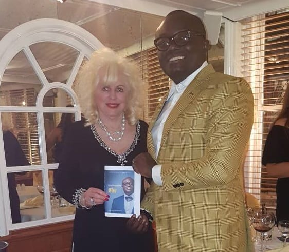 Bola Ray presents copy of Biography to World Renowned Cosmetologist Dr. Rita Rakus