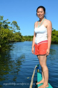 Me standing at the tip of the small boat and posing near the mangroves