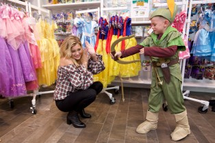 In this photo provided by Nintendo of America, Hollywood Records recording artist Olivia Holt helps a young fan get dressed up as their favorite Disney character at the Enchanted Ball Event for the Disney Magical World 2 game on Oct. 1 at Nintendo NY. The magical event celebrated the upcoming launch of the game for the Nintendo 3DS family of systems on Oct. 14.