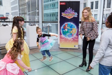 In this photo provided by Nintendo of America, Oliva Holt has a first dance with young fans at the Enchanted Ball Event at Nintendo NY to celebrate the upcoming launch of the Disney Magical World 2 game for the Nintendo 3DS family of systems on Oct. 14.