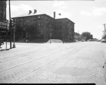 Historic photo displaying streetcar tracks at Park Avenue and Leavenworth Street, looking southwest at the Barnard Apartments, the Portland Apartments just to the south. Creator: Bostwick, Louis (1868-1943) and Frohardt, Homer (1885-1972). Publisher: The Durham Museum. Date: 1951. These apartments are now called the The Barnard Flats at 804 Park Avenue. Like its half-sister building, the Unitah across to the north, The Barnard also has doors on Park Avenue and Leavenworth Street.