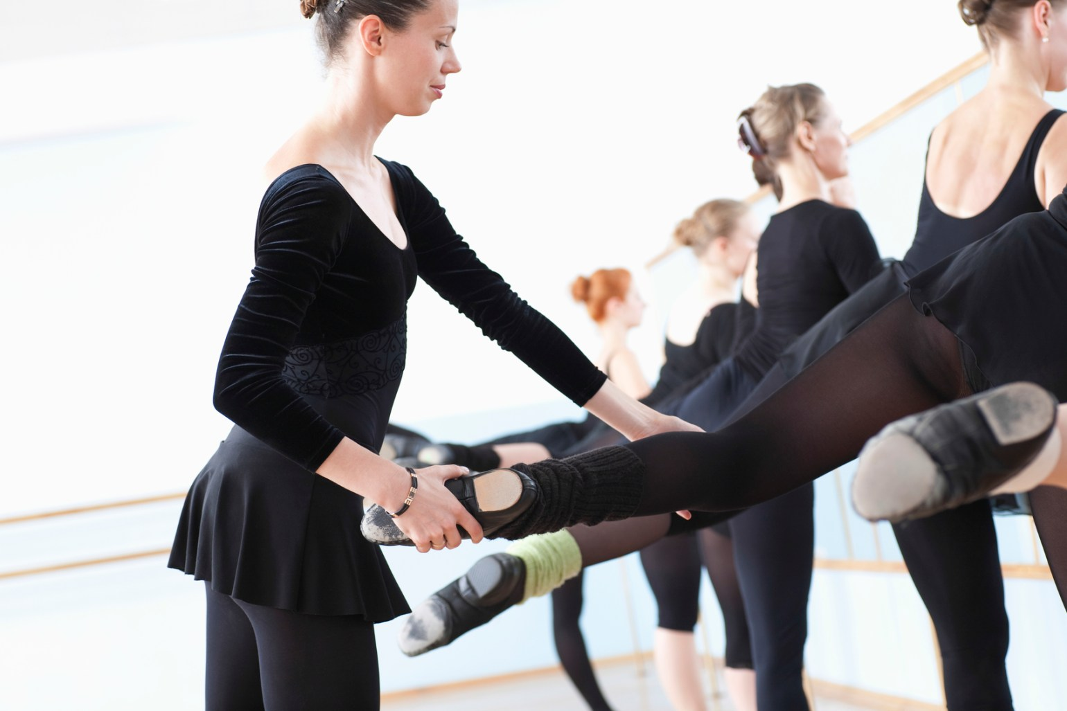 Ballet Teacher Adjusting Foot Positions Of Ballerinas