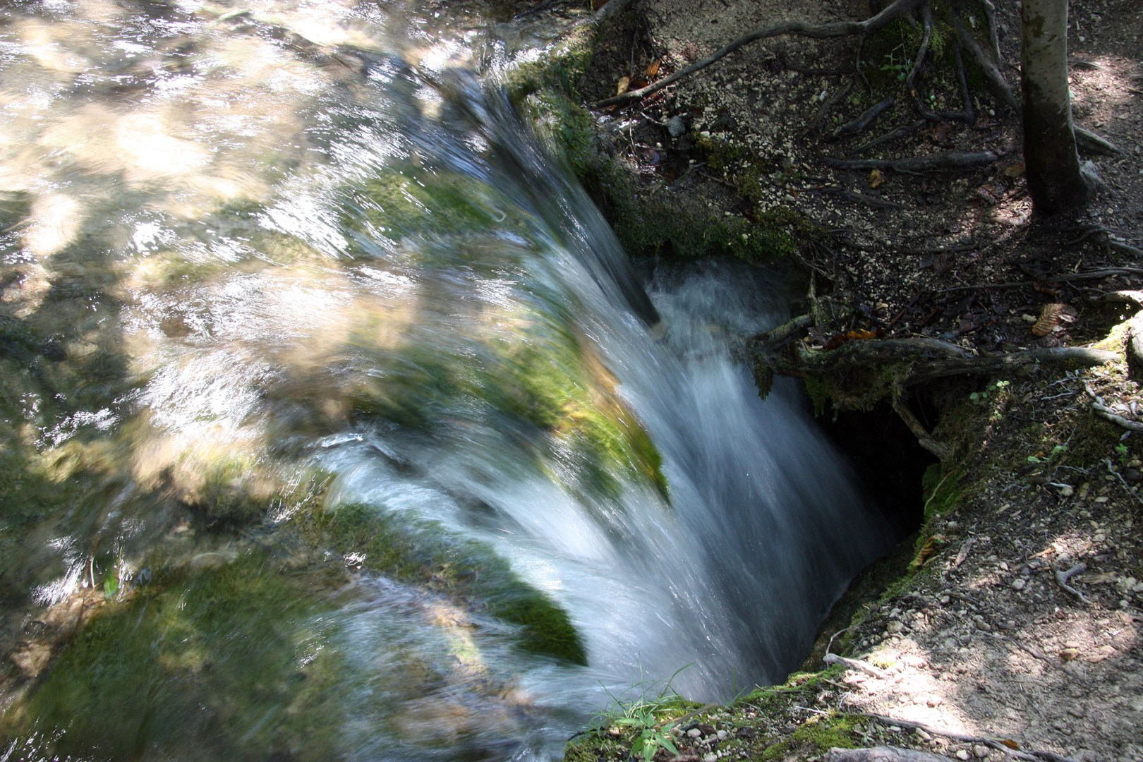 Water flowing down a hole in the ground
