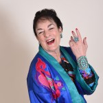 Picture of Nancy Wyatt, in coat of many colors showing turquoise ring and bracelet created by Native Americans. S he's showing the plant care video