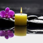 burning yellow candle with purple orchid on black rocks and water