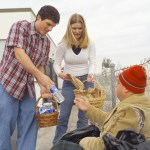 homeless man receiving food and water from couple