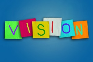 The word VISION written in colorful sticky notes on a blue background for classes in a training venue