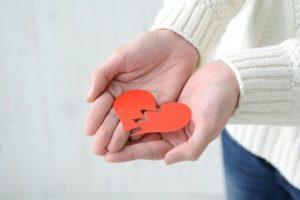 hands holding a red broken heart