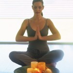 woman meditating with candle and water