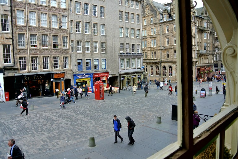 A red telephone box and people in the street on Edinburgh's Royal Mile.