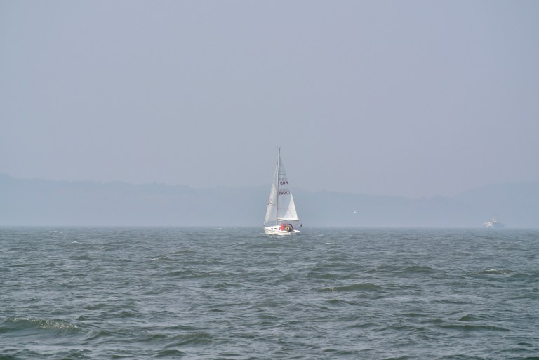 A white sailboat in the Firth of Forth.