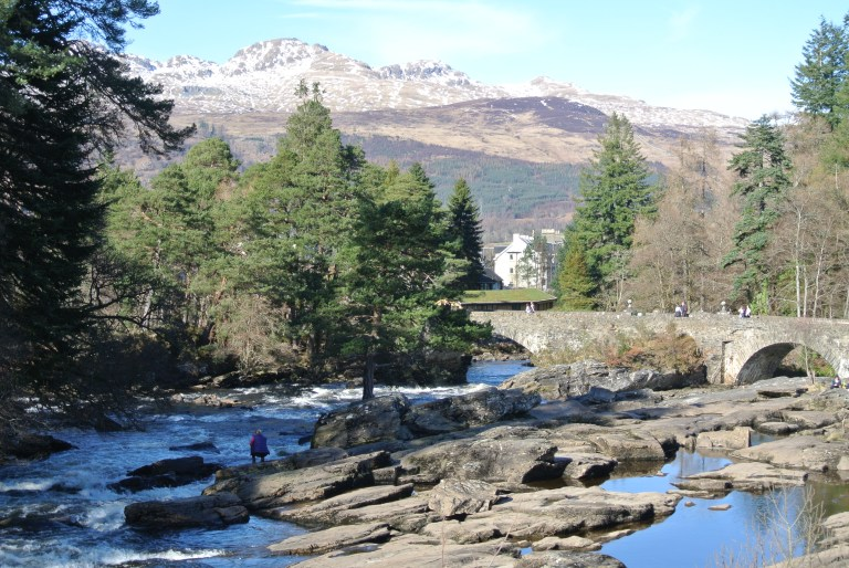 View of the rocks and bridge at the Falls of Dochart with snow capped mountains behind.