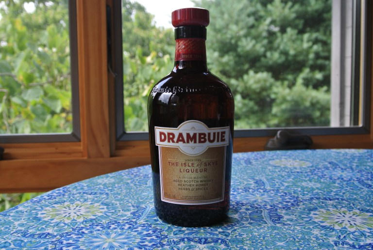A bottle of Drambuie on a blue floral tablecloth.