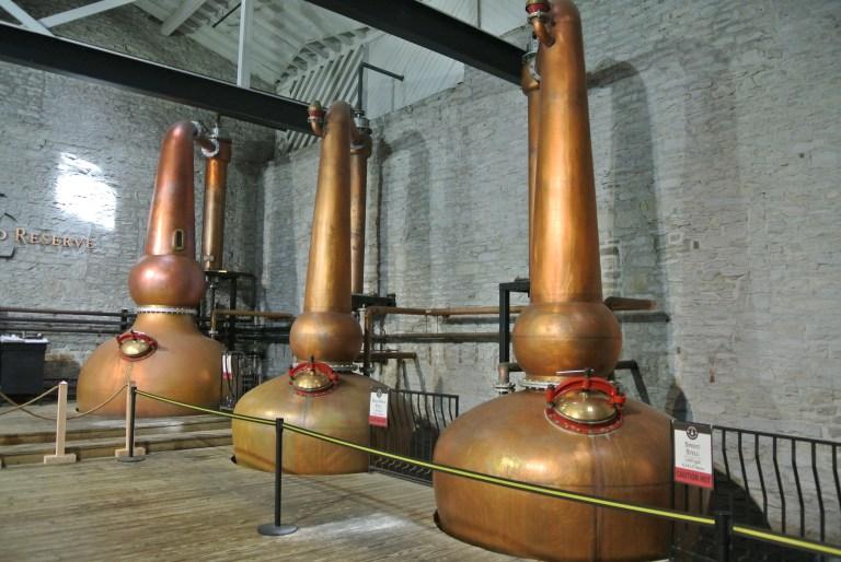 Three tall copper whiskey stills.
