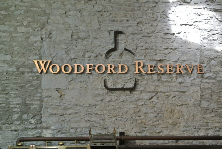 A stone wall with a Woodford Reserve sign.