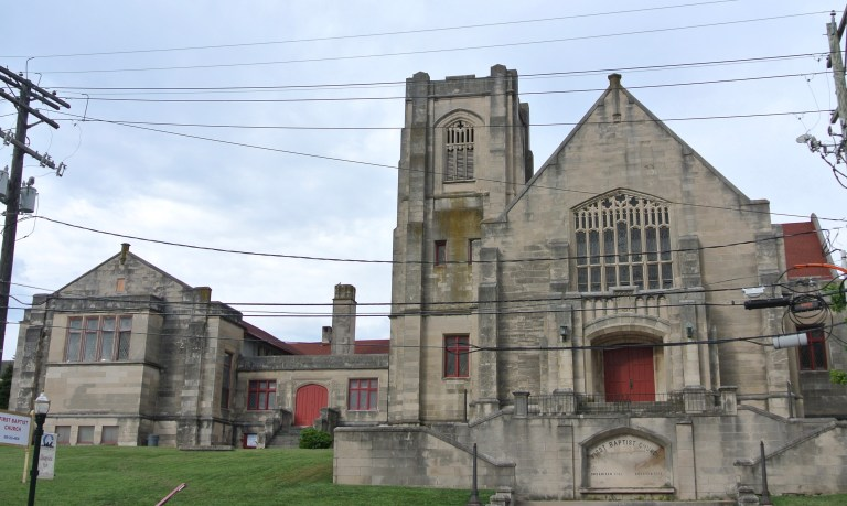 An old gray stone church with red doors.