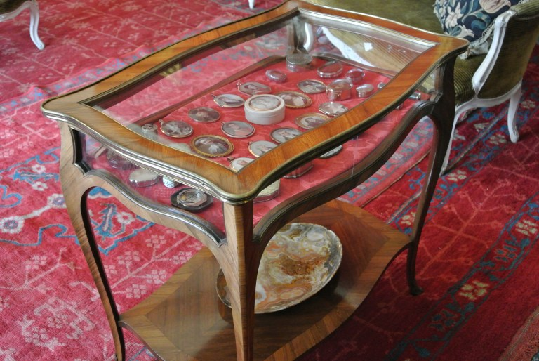 A collection of antiques inside a brown table with a glass top.