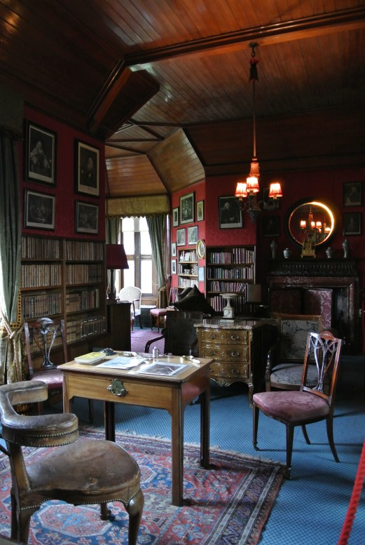 A red and blue library full of antique books at Lauriston Castle.