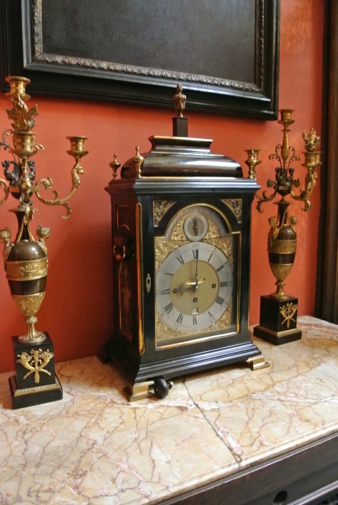 An antique clock and two ornate candlesticks on a marble topped table.