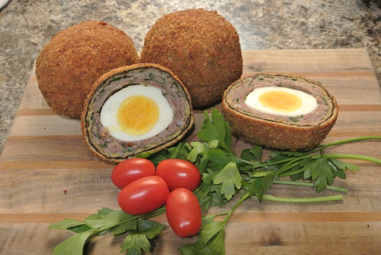 Three Scotch Eggs on a wooden board that has been decorated with cherry tomatoes and herbs.