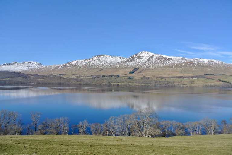Snow capped mountains and blue sky reflecting on the water of Loch Tay.