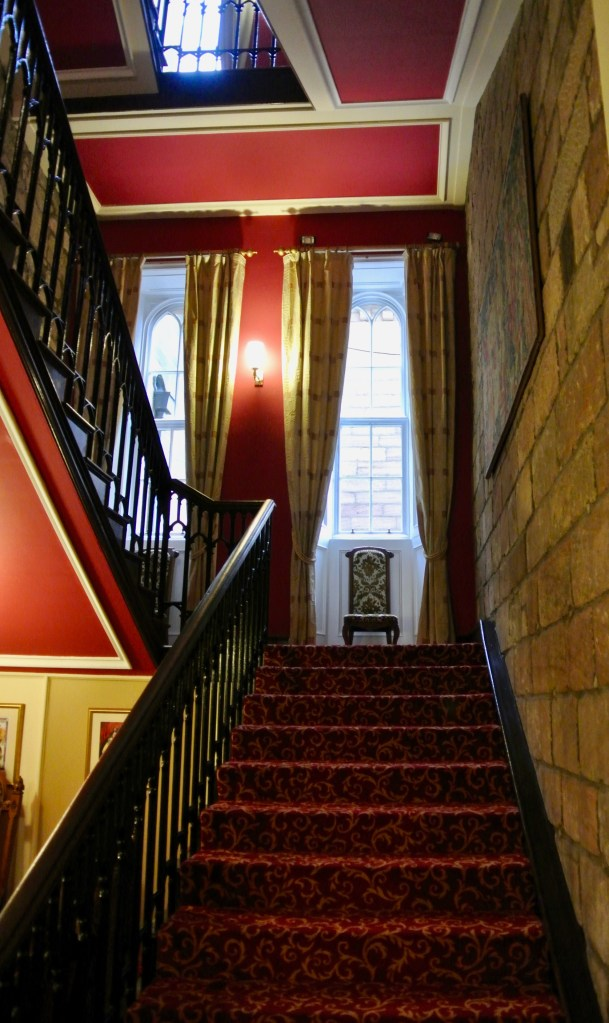 Castle staircase with red carpet.