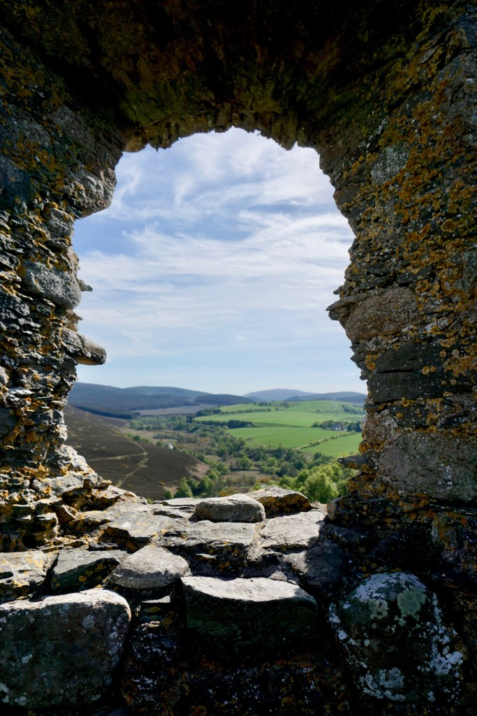 A window at Auchindoun Castle that looks out over the Scottish countryside.