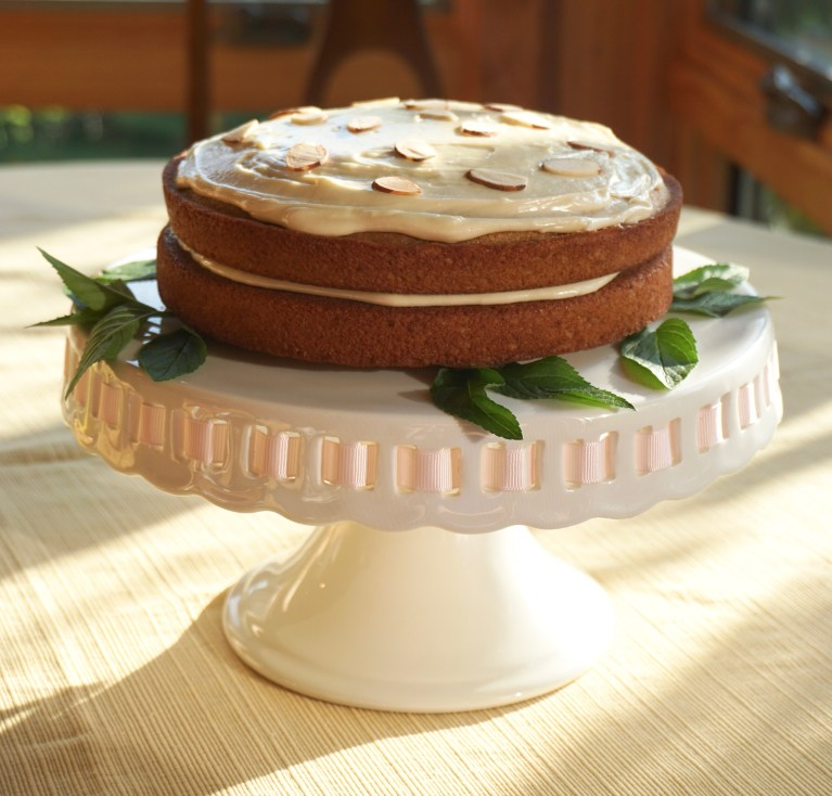 An iced honey and whisky cake on a white cake stand.