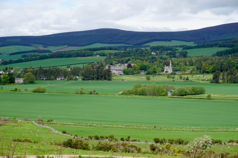 The green Scottish countryside and the village of Tarland in the distance.
