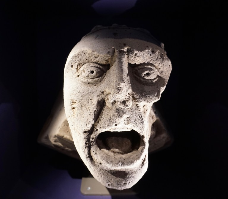A stone carving of a face with it's mouth open- a vault boss at Elgin Cathedral.