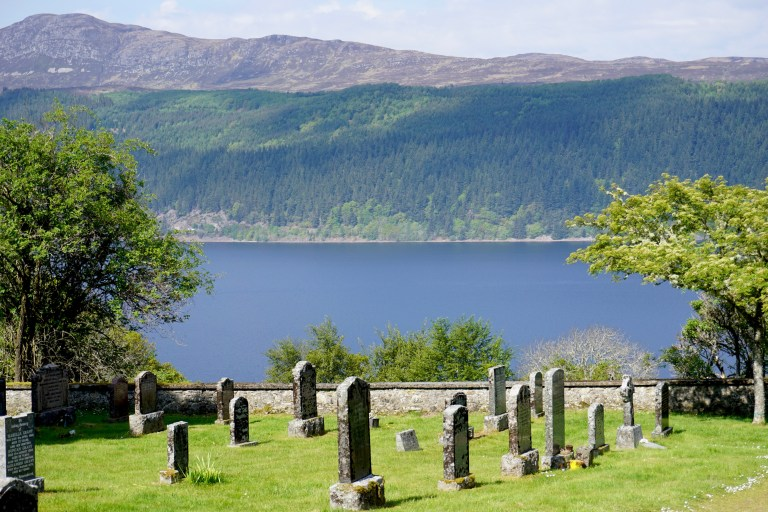 Loch Ness and gravestones at Boleskine Cemetery.