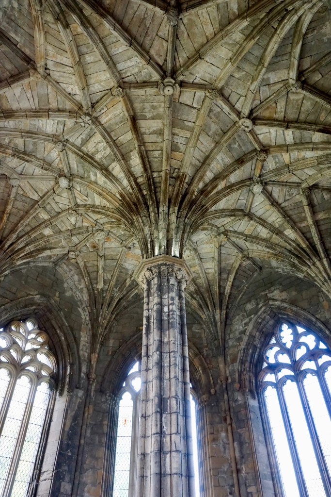A column, ornate windows, and an intricate stone ceiling at Elgin Cathedral.