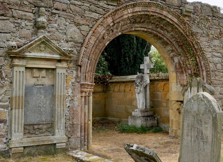 An arched doorway at Kinloss Abbey and a headless angel grave marker.