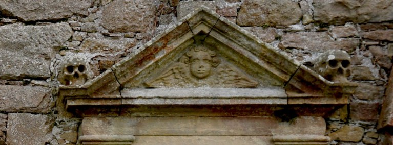 A skull and face carvings over a doorway at Kinloss Abbey.