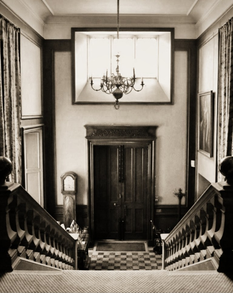 A large wooden front door, a chandelier, and a staircase inside the Lauriston Castle entrance.