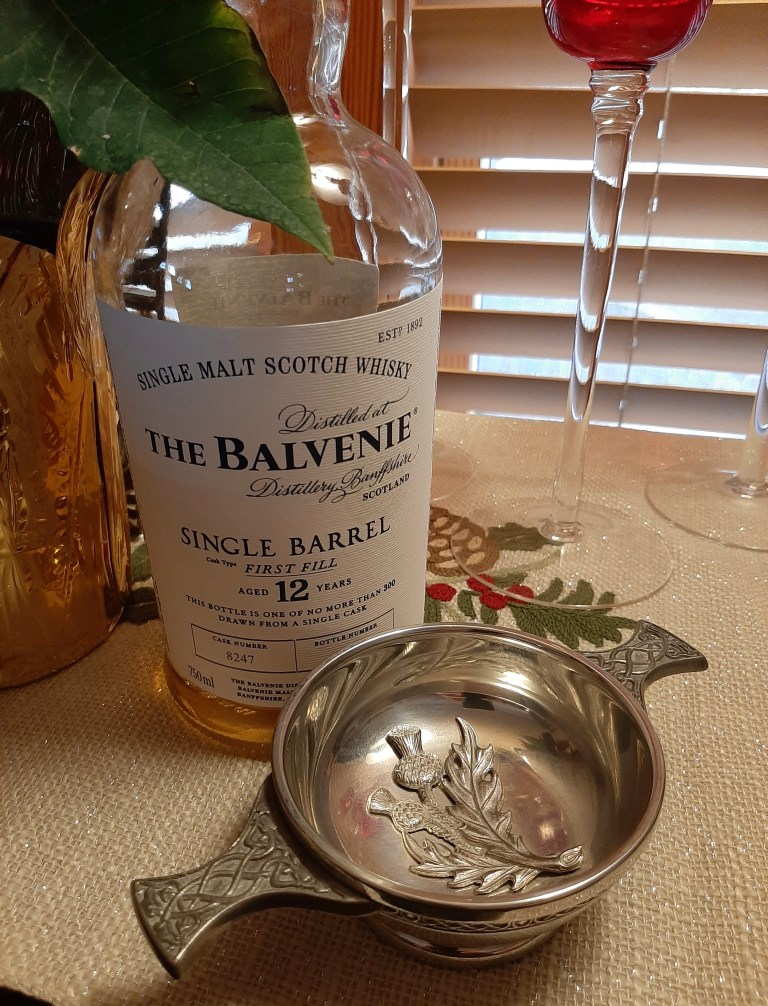 A bottle of Balvenie whisky next to a pewter quaich, also known as a Scottish Cup of Friendship.