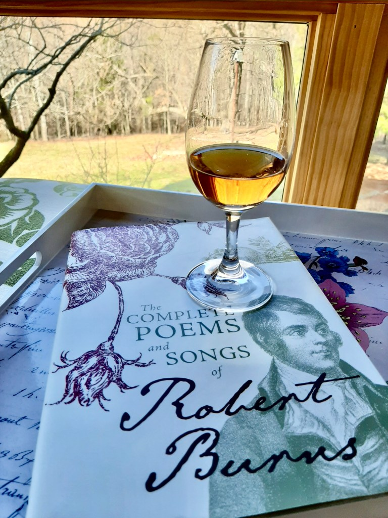 A glass of Scotch on a book of poems and songs by Robert Burns.