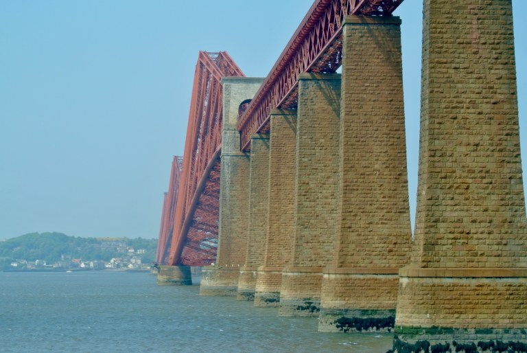 Massive columns supporting the red Forth Bridge in the Firth of Forth.