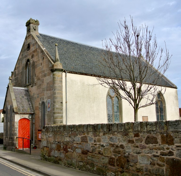 A church with a bright red door in Pittenweem, Scotland.