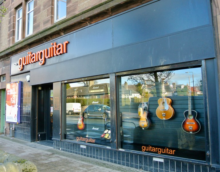 The storefront windows of a guitar store in Corstorphine, Scotland.