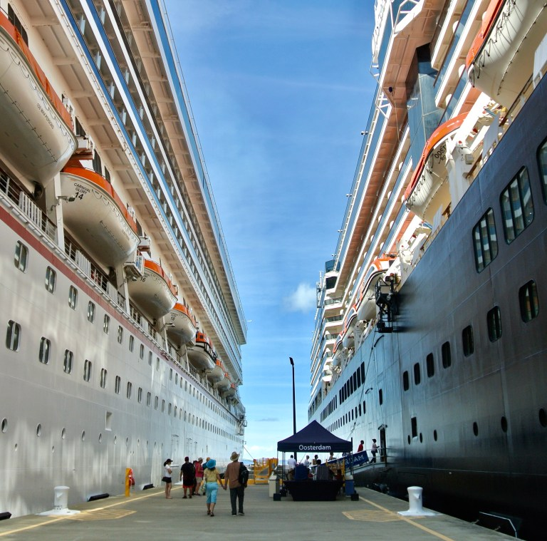 A man and woman holding hands, walking between two docked cruise ships.